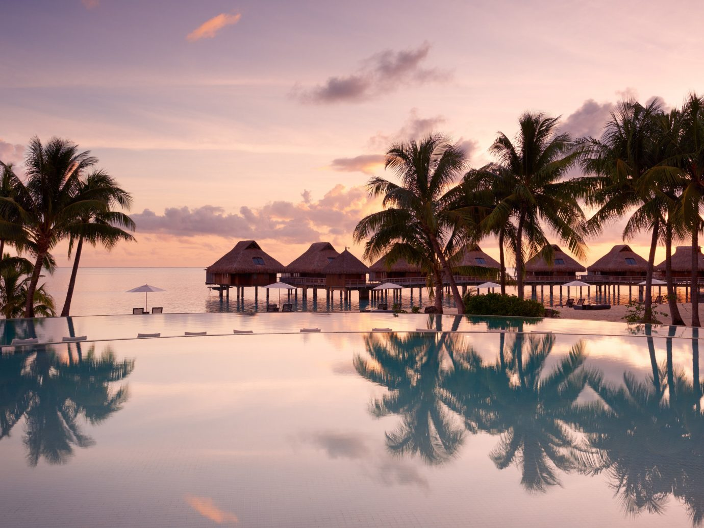 Hotels tree outdoor sky water reflection tropics plant palm palm tree Sunset arecales Resort vacation Sea evening caribbean morning horizon dusk Ocean tourism sunrise setting calm computer wallpaper dawn cloud leisure Lagoon shore several