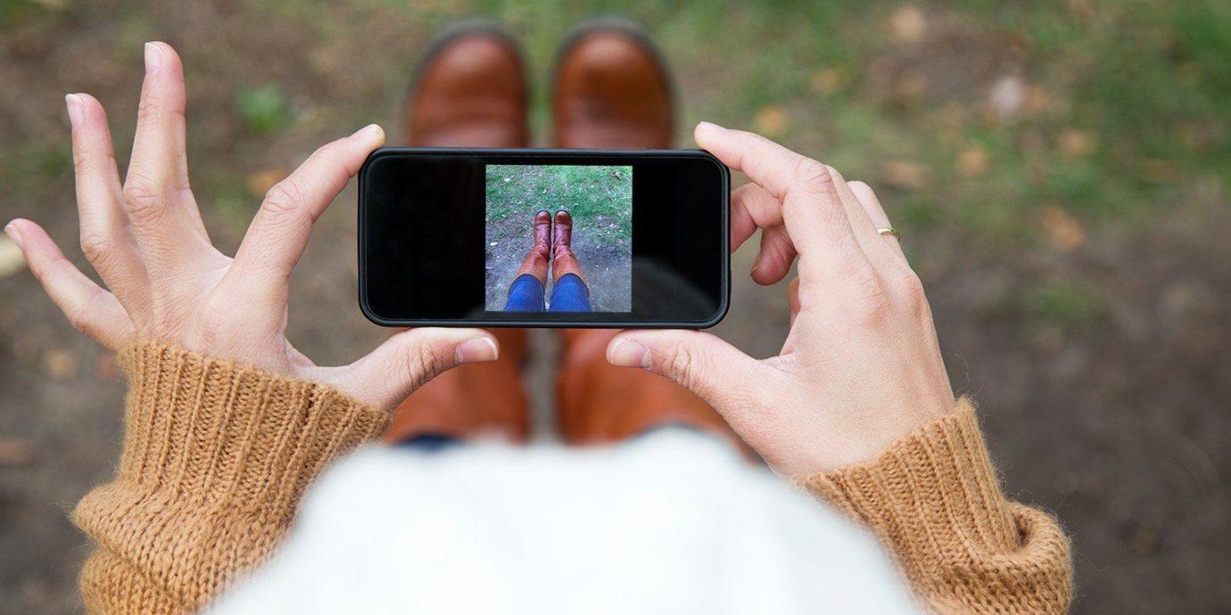 Offbeat cellphone phone person grass outdoor finger hand eye