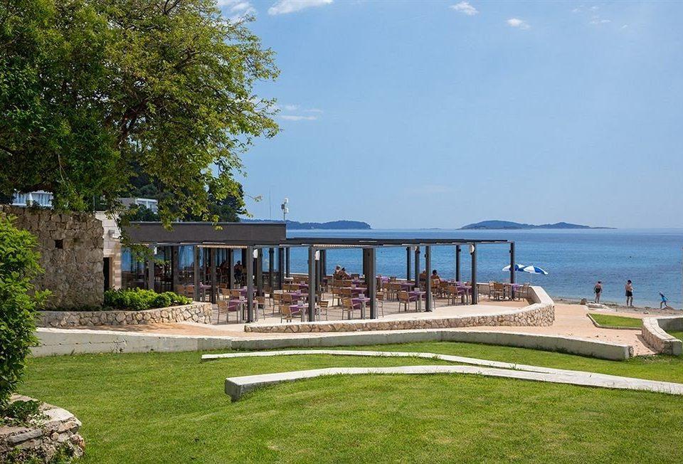 grass tree sky property park lawn walkway Resort home Villa Sea shore stone