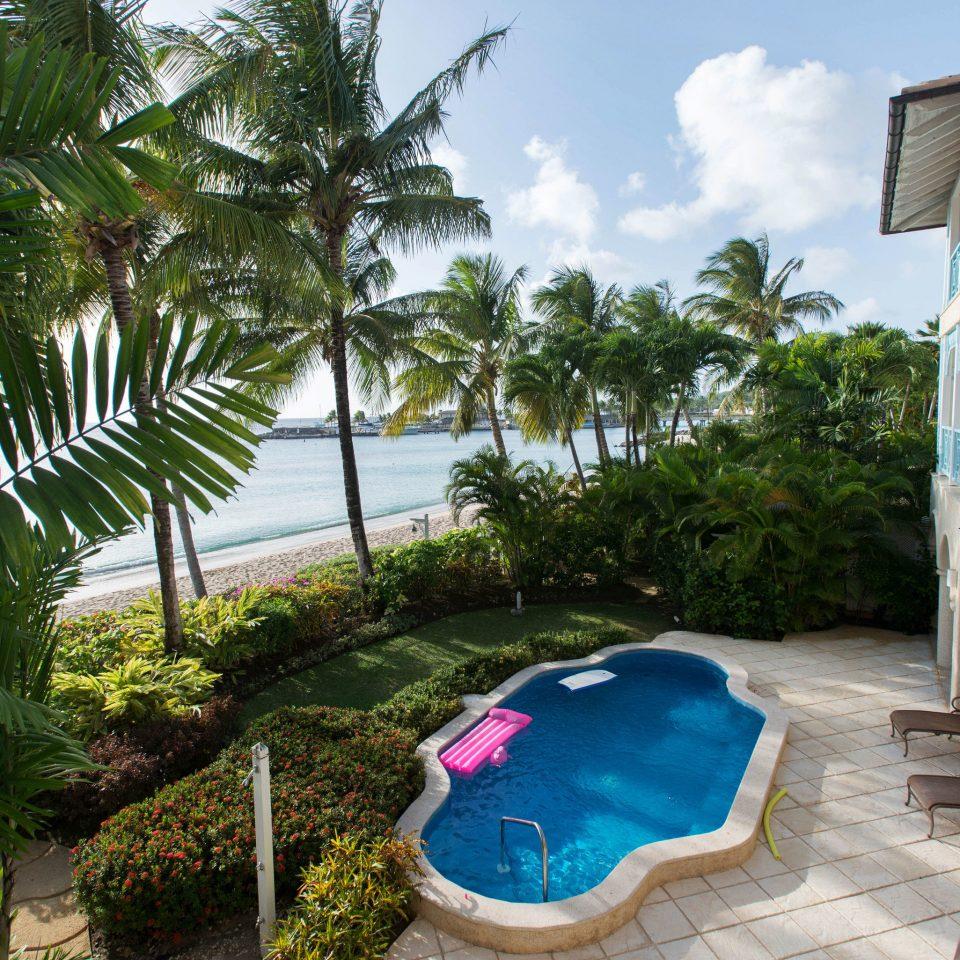 tree swimming pool property Resort Villa caribbean palm arecales backyard home plant mansion condominium hacienda shade stone