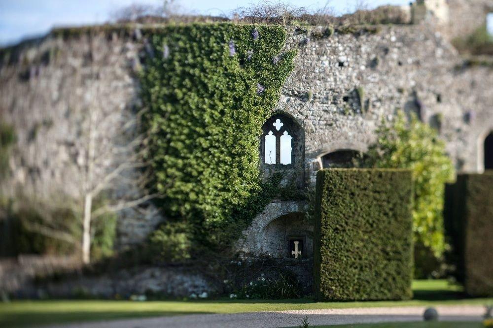 building stone grass tree rock brick castle plant fortification Ruins Village château sky shrub landscape cement