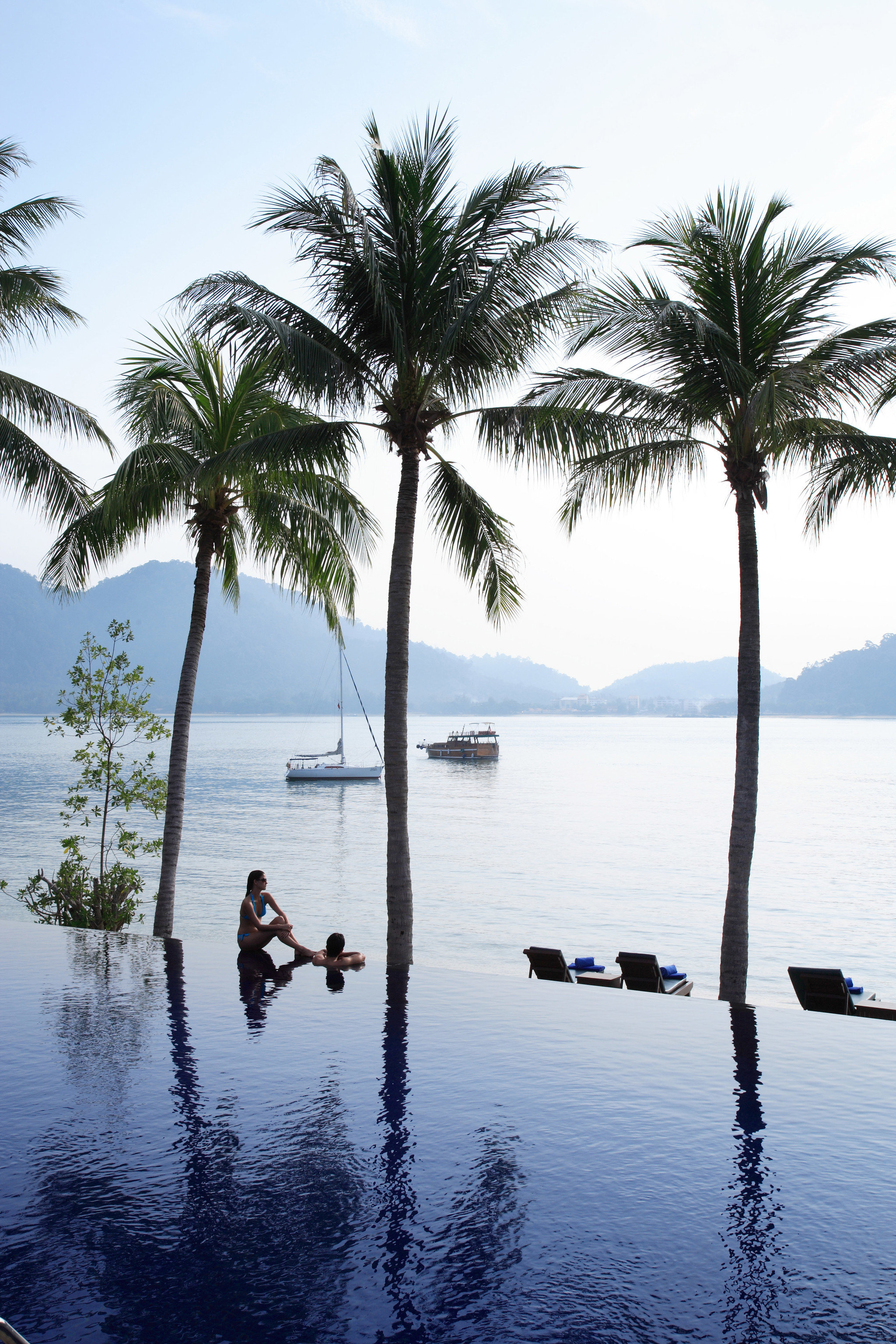 Hotels water sky outdoor tree plant Boat Lake palm body of water shore palm family Sea Beach Ocean vacation arecales woody plant Coast land plant reflection bay tropics Lagoon flowering plant day