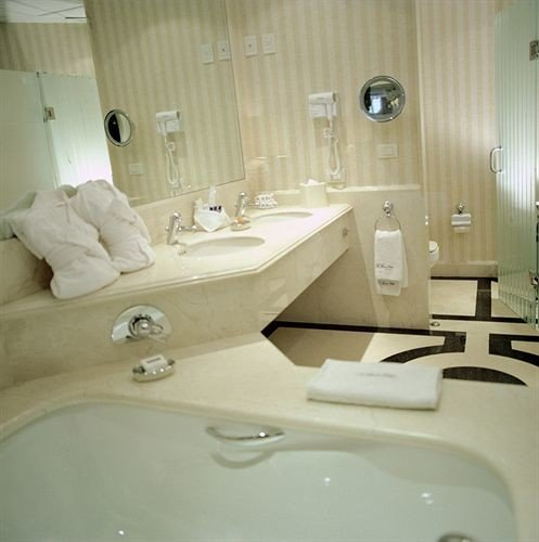 bathroom sink toilet mirror property swimming pool bathtub white jacuzzi bidet plumbing fixture Suite towel tiled