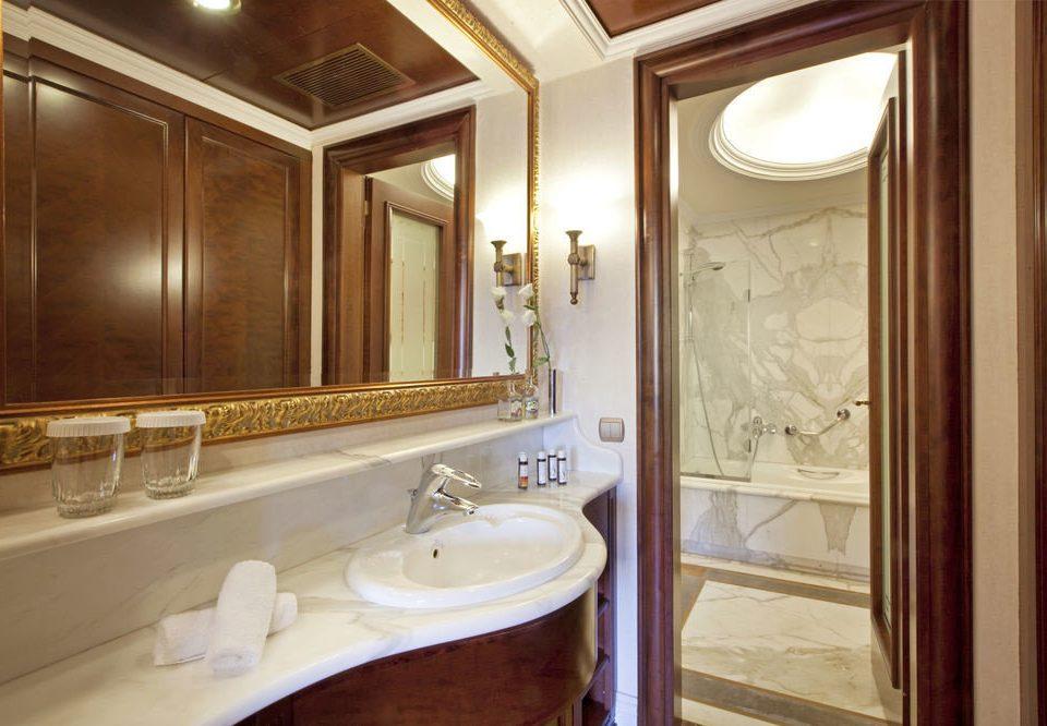 bathroom mirror sink property Suite cabinetry home toilet tub bathtub tan