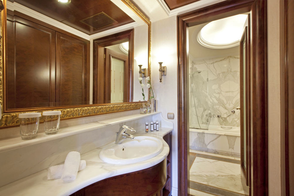 bathroom mirror sink property Suite cabinetry home toilet tub bathtub tan