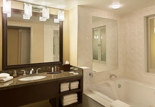 bathroom mirror sink property home Suite countertop cabinetry cottage tub bathtub clean tan tile