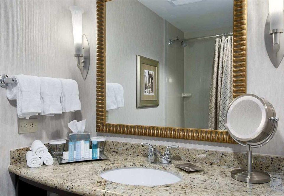 bathroom sink mirror property Suite home counter towel plumbing fixture cottage bathtub flooring vanity dining table