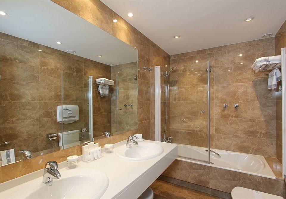 bathroom sink mirror property toilet plumbing fixture bathtub Suite flooring counter tan