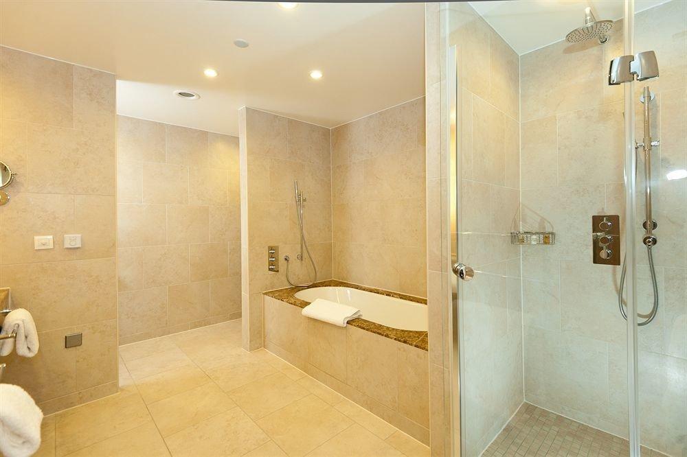 bathroom scene property plumbing fixture Suite sink bathtub flooring toilet tan tiled