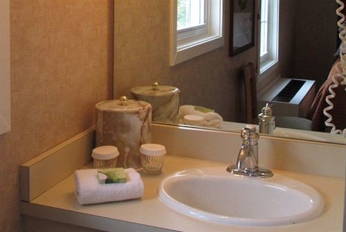 bathroom sink property mirror home plumbing fixture flooring toilet Suite