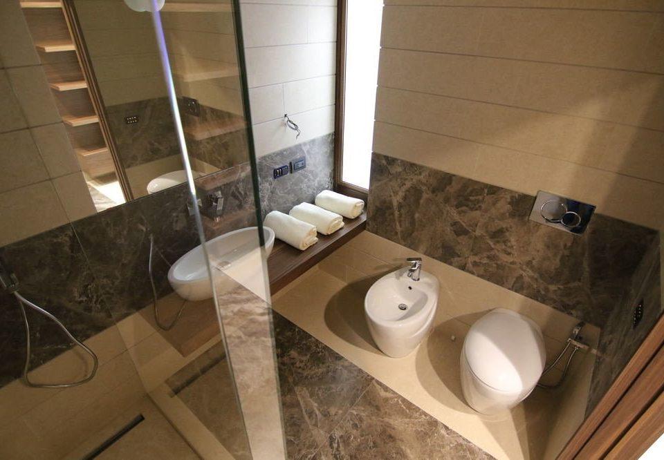bathroom property sink toilet plumbing fixture flooring Suite tiled tile