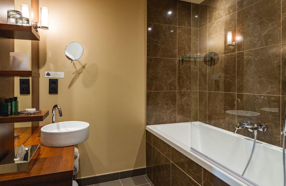bathroom property sink plumbing fixture Suite flooring tile tiled tub