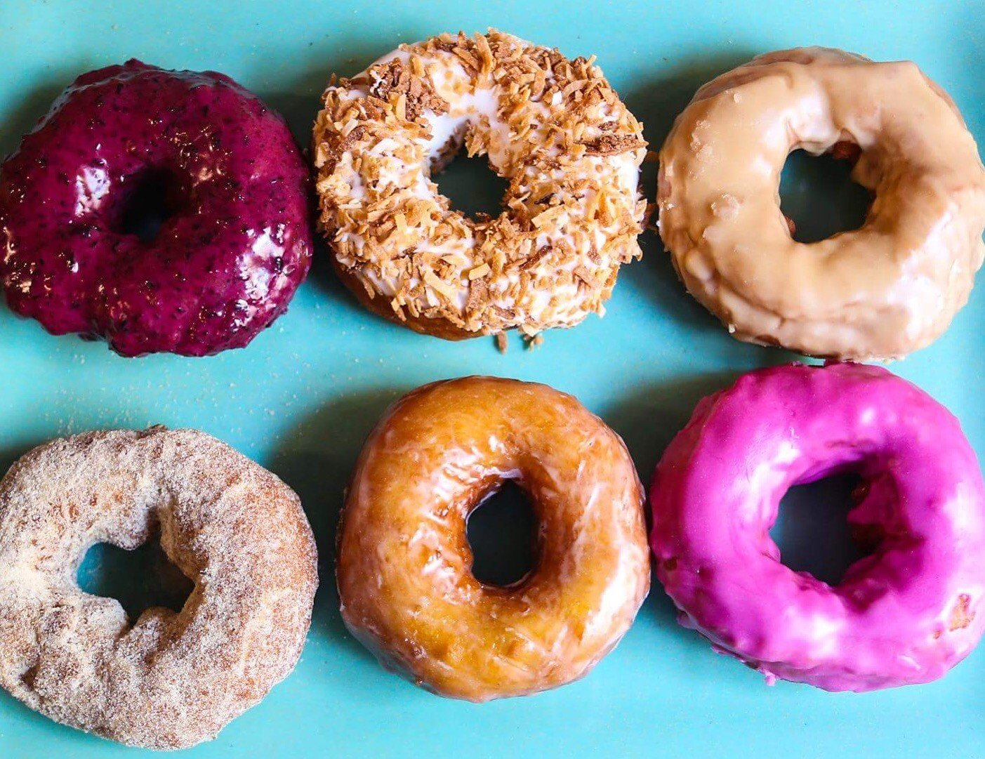 bakery comfort food dessert Dining donuts Eat food Food + Drink Health + Wellness sweets Travel Tips doughnut donut baked goods pink plain produce bagel pastry snack food assorted different few rack toppings lined colored variety