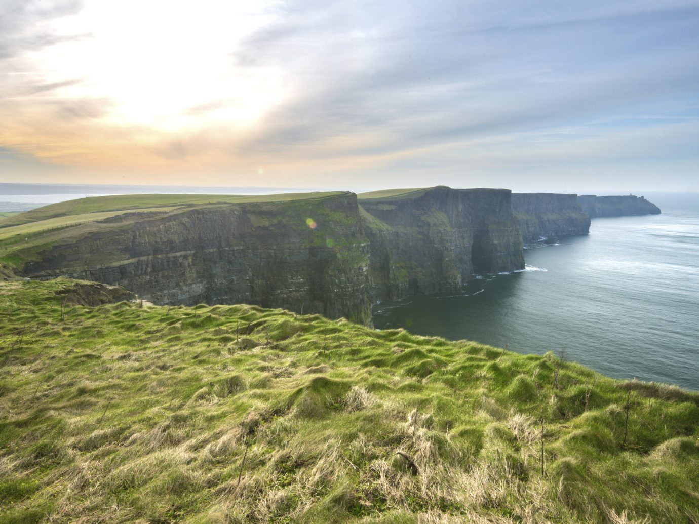 Offbeat grass sky outdoor water Nature Coast cliff hill landform geographical feature atmospheric phenomenon Sea body of water green shore horizon Ocean grassy terrain loch cloud reservoir bay hillside landscape cape fjord waterway lush overlooking rock pasture day highland