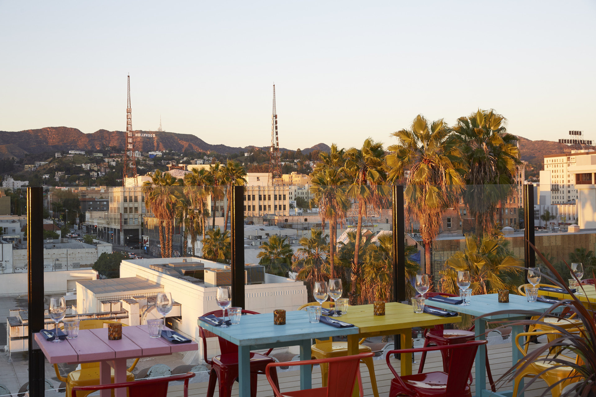 Boutique city views Dining glow golden hour Hip outdoor dining palm trees Rooftop Sunset tables Travel Tips trendy Tropical view outdoor sky Town plaza City neighbourhood urban area human settlement cityscape Harbor Downtown town square skyline several day