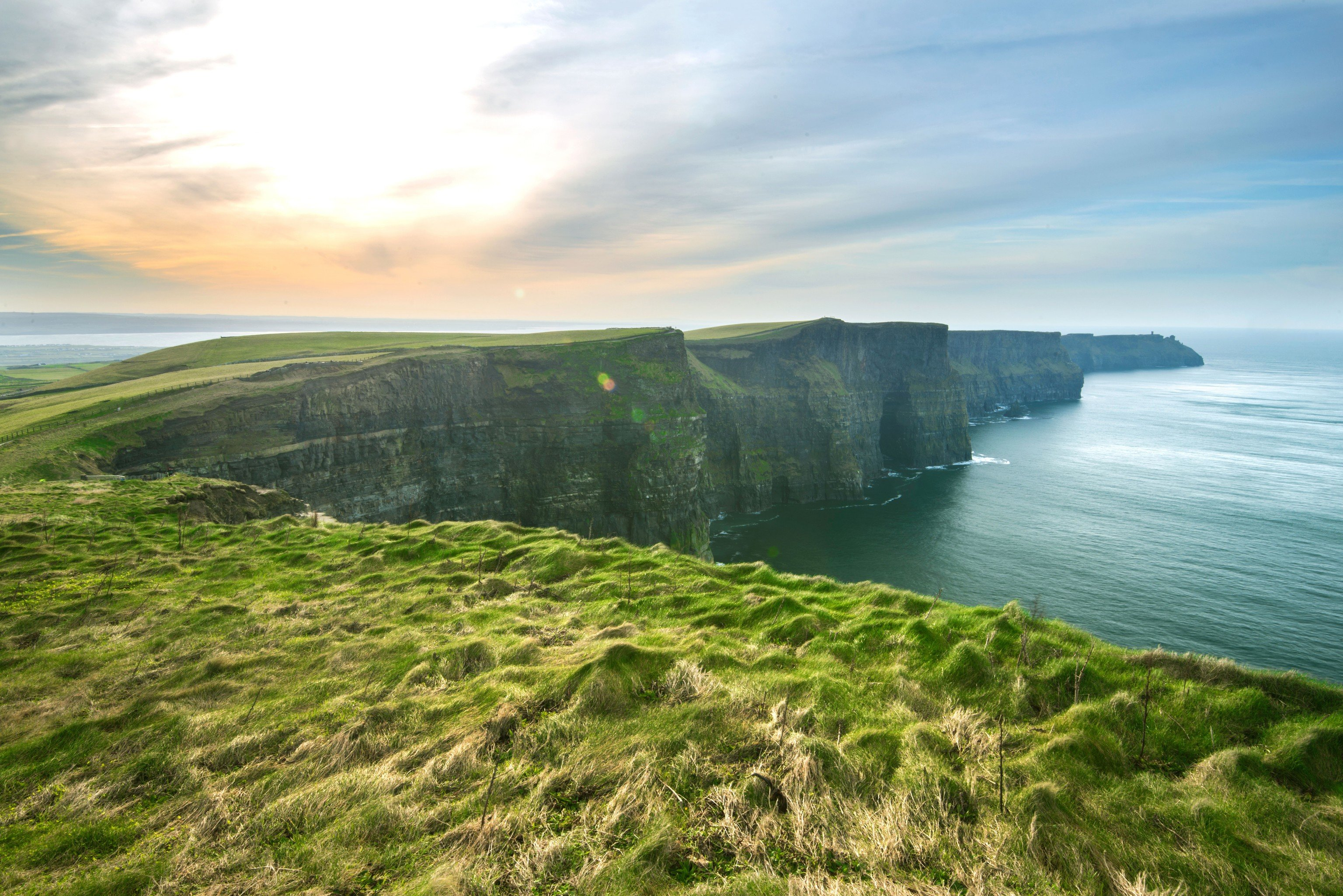 Jetsetter Guides grass sky outdoor water Nature Coast cliff landform geographical feature atmospheric phenomenon Sea body of water horizon shore hill green Ocean cloud grassy terrain loch morning reservoir bay landscape cape fjord hillside cove Lake overlooking lush rock highland