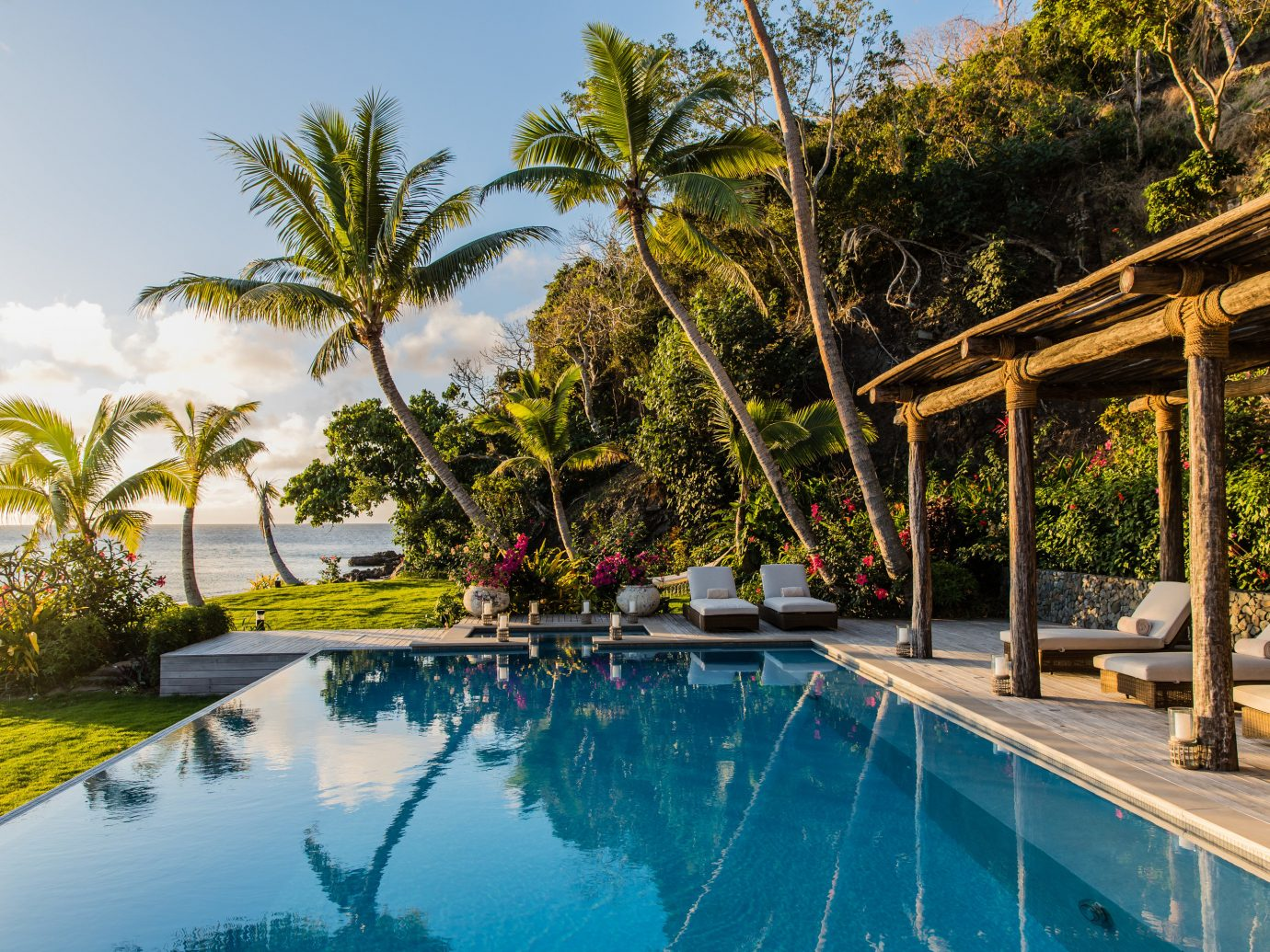 Boutique Hotels Hotels Luxury Travel tree outdoor sky Resort swimming pool property palm tree estate arecales leisure real estate Villa tropics vacation resort town plant water hacienda cottage amenity