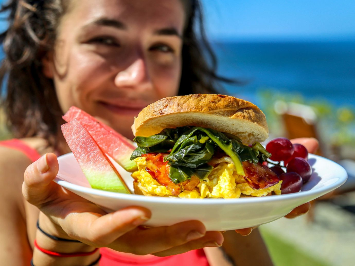 Health + Wellness Meditation Retreats Trip Ideas Yoga Retreats person outdoor food human action dish snack food eating sandwich meal lunch cuisine breakfast produce fast food sense junk food