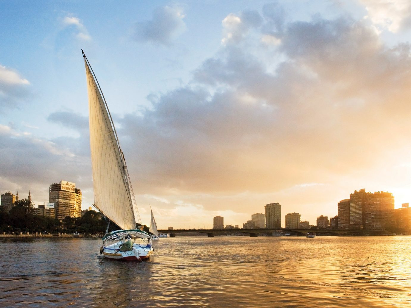 Lakes + Rivers Landmarks sky water outdoor Boat sailboat reflection horizon vehicle sail Sea morning cityscape River evening skyline dusk sailing vessel skyscraper sunlight Sunset waterway sailing day distance