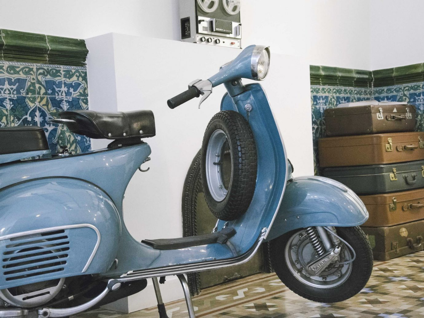 Hotels scooter vespa car indoor parked automotive design motorcycle vehicle blue automobile make seat tiled
