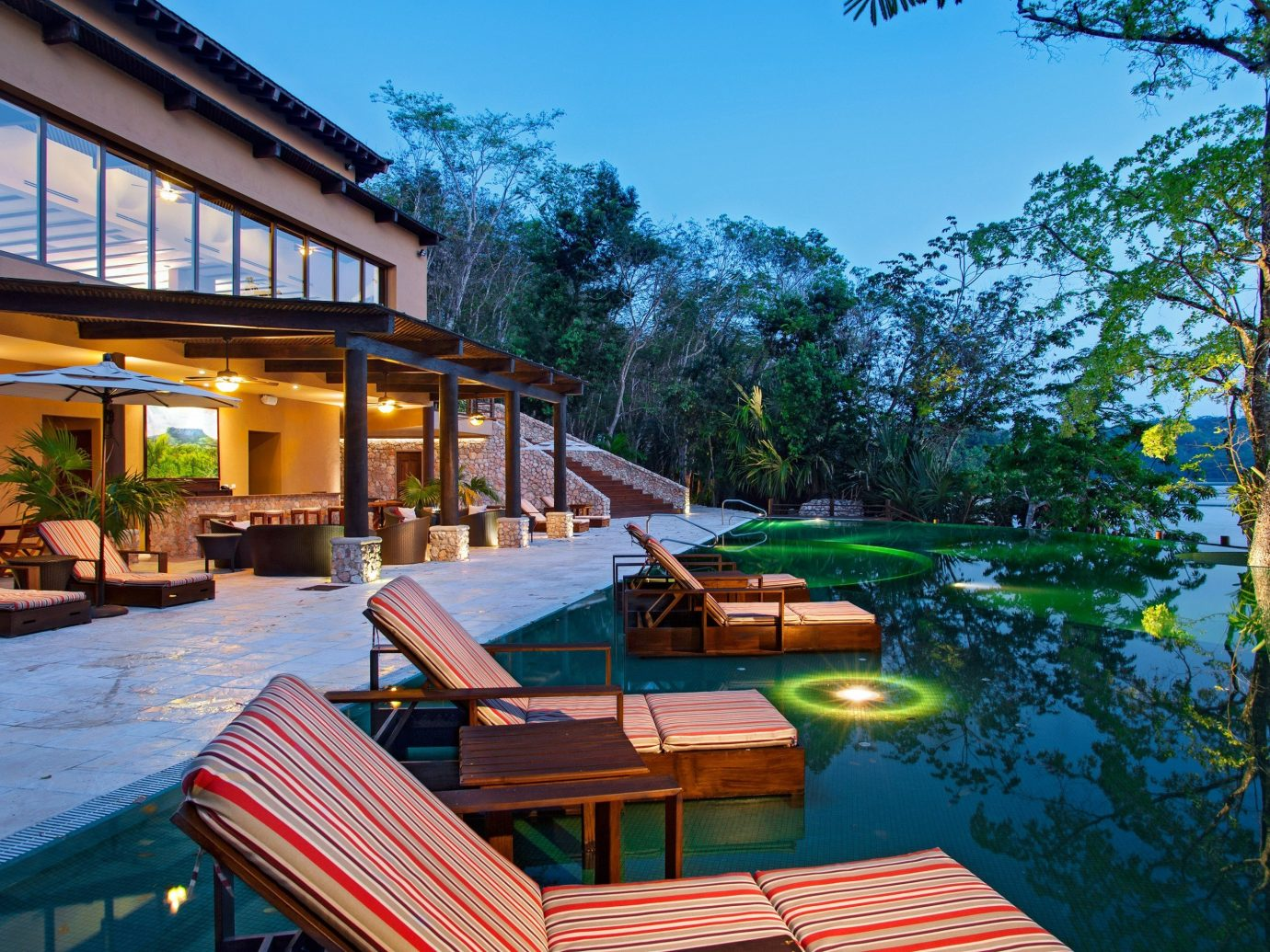 Hotels Outdoors + Adventure tree outdoor leisure property Resort swimming pool estate house vacation home real estate Villa eco hotel cottage condominium backyard area furniture several
