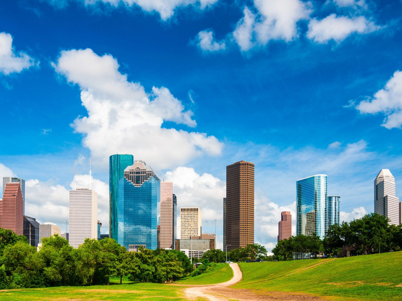Houston Outdoors + Adventure Texas Trip Ideas metropolitan area sky daytime skyline landmark cloud skyscraper City urban area cityscape metropolis tower block grass residential area horizon Downtown corporate headquarters meadow condominium tree real estate building landscape computer wallpaper cumulus meteorological phenomenon energy suburb