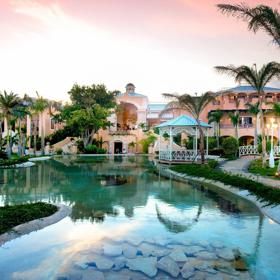 Resort water property swimming pool palm tree sky arecales home leisure tree mansion tropics Villa hacienda resort town evening plant landscape house
