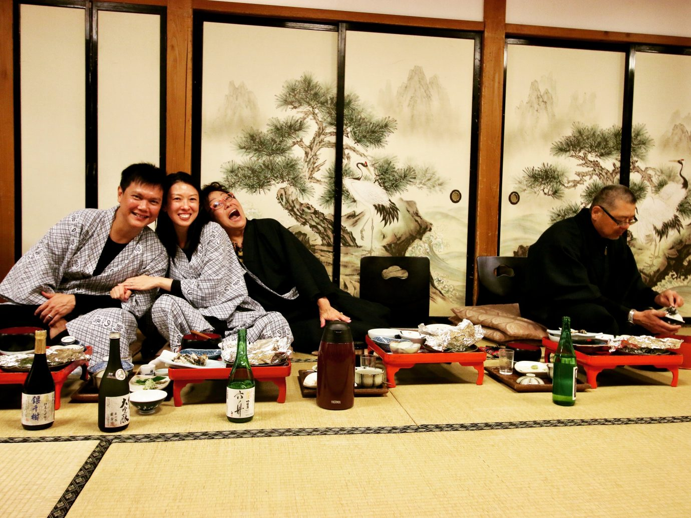 people eating dinner and drinking sake in japan