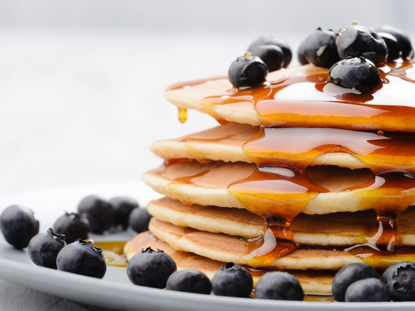 Plate of delicious pancakes close up, with fresh blueberries and maple syrup dripping