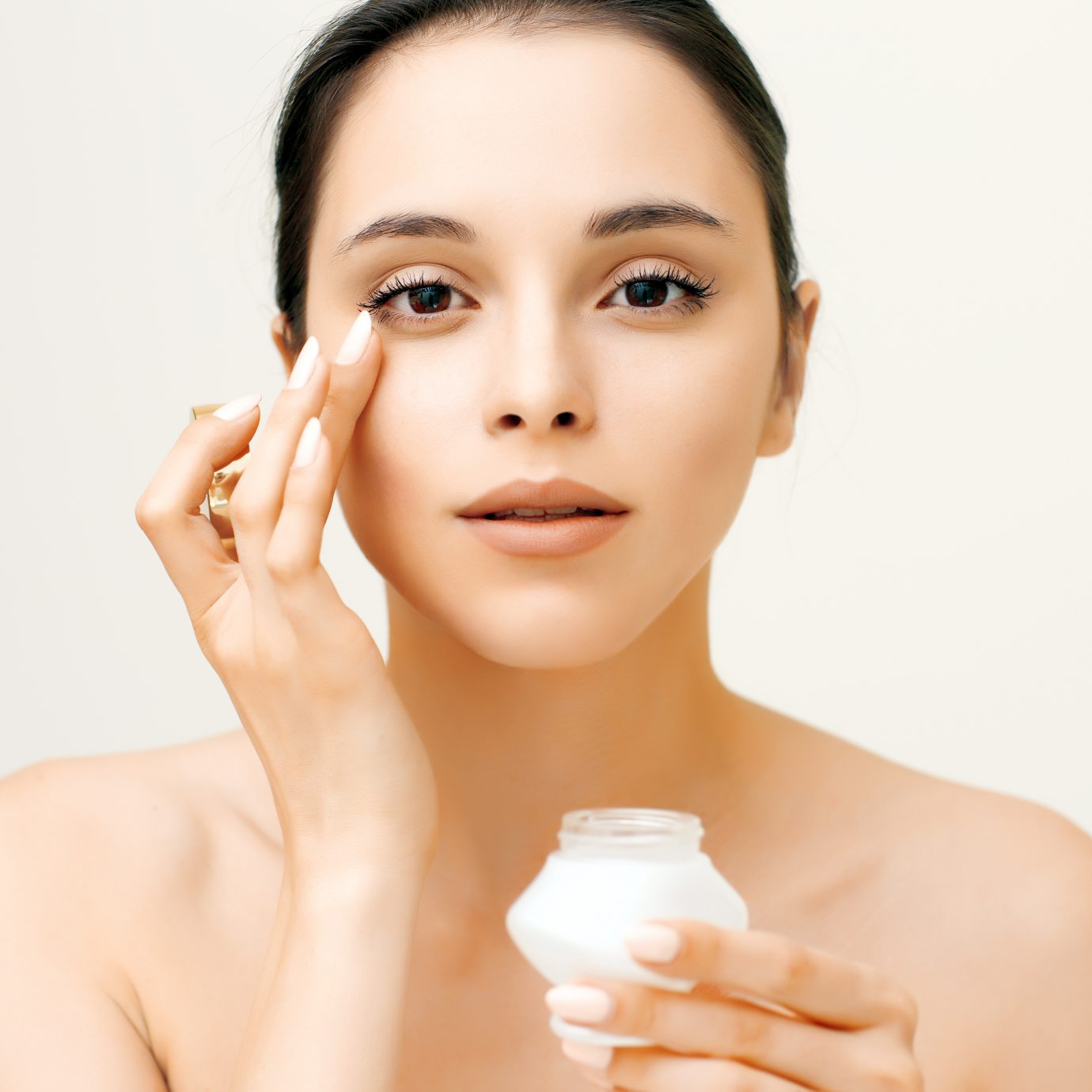 Natural beauty portrait of young woman applying cream on her face, Eye creams with SPF