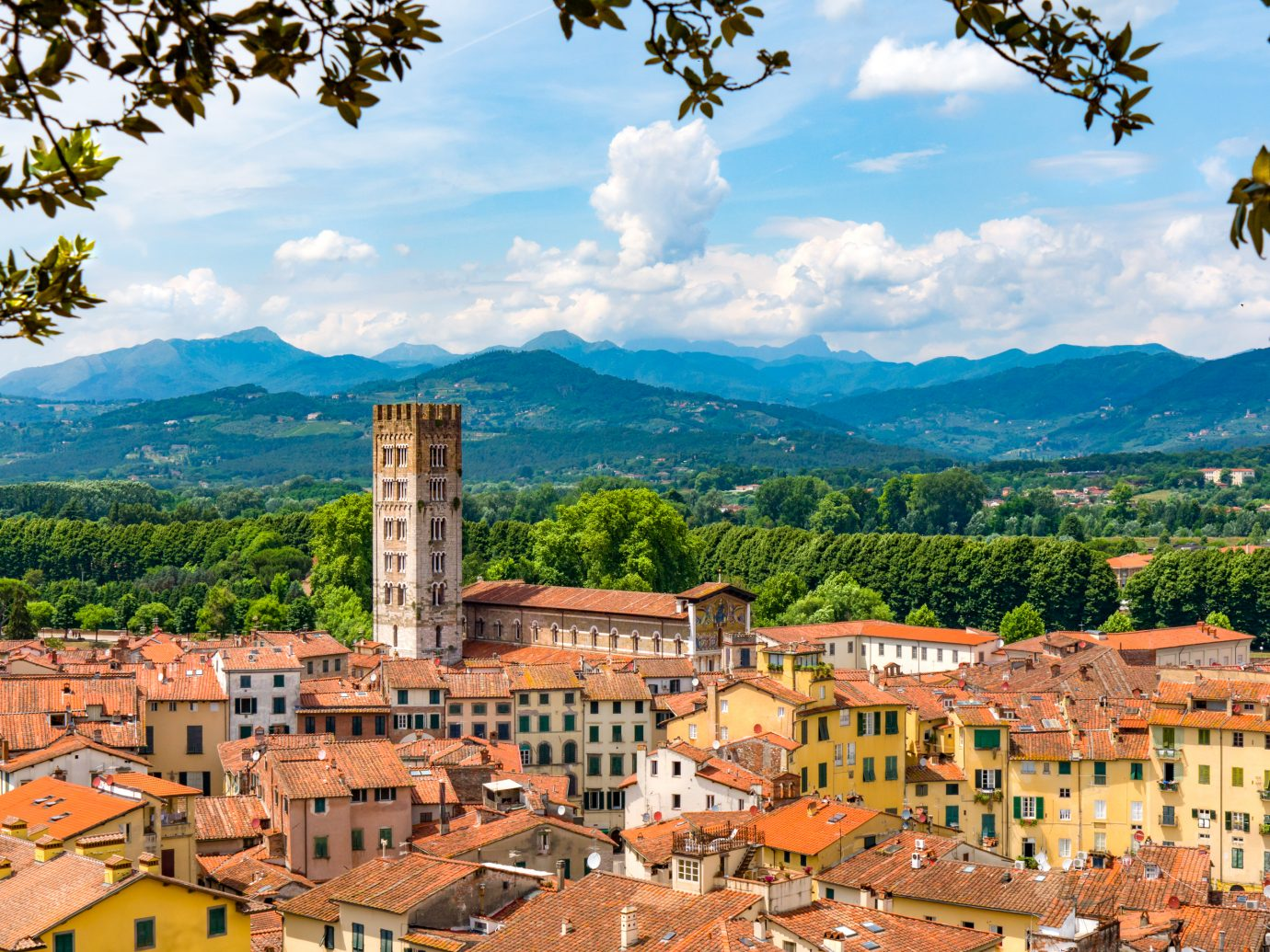A view of the rooftops of the quaint Tuscan town of Lucca, Italy with mountain landscape in the background