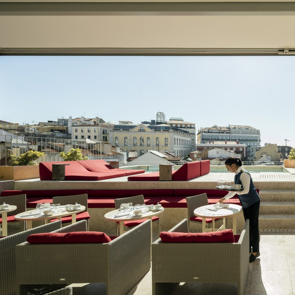 Red outdoor seating near rooftop pool with waiter setting up tables at Verride Palácio Santa Catarina