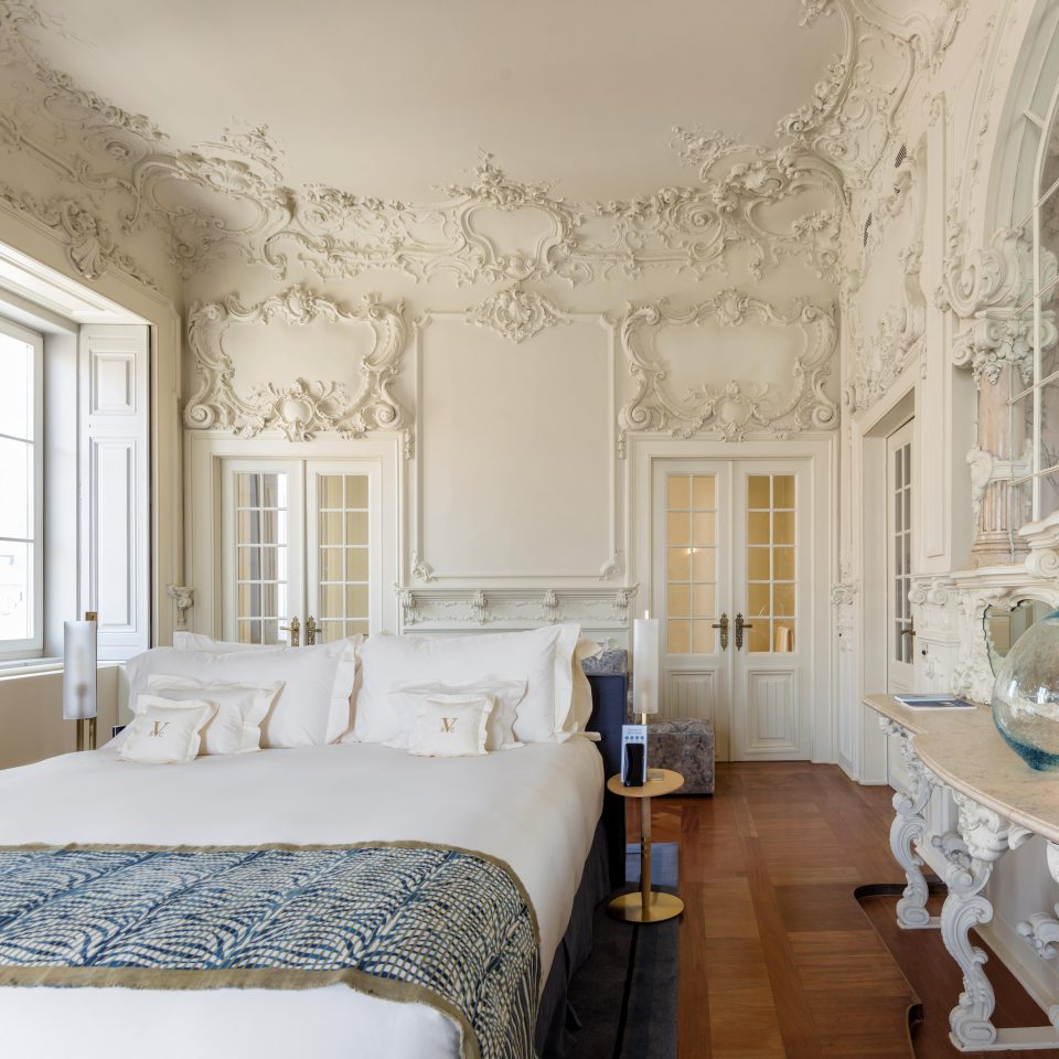 Luxurious white room with wall accents and bed at Verride Palácio Santa Catarina