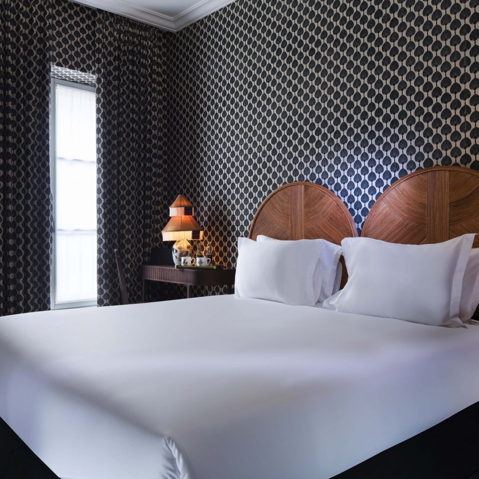 White bed with black and white wall decor, Hôtel Monte Cristo
