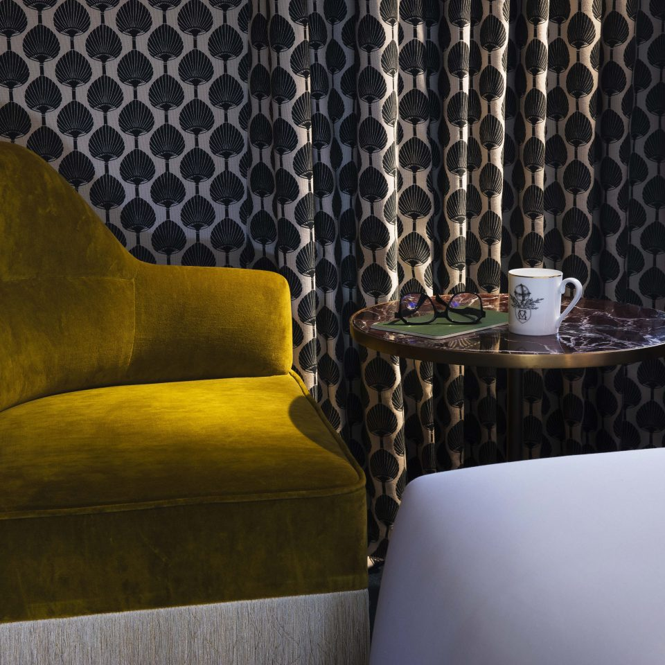 Faded lime green corner chair with coffee and reading glasses, Hôtel Monte Cristo