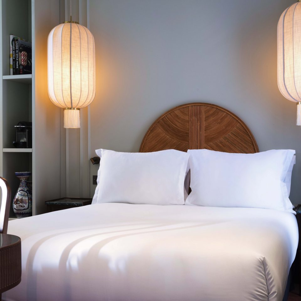 White bed with paper lanterns in room at Hôtel Monte Cristo