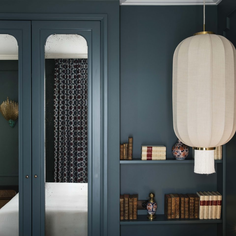 Door with double mirrors and small library in room at Hôtel Monte Cristo