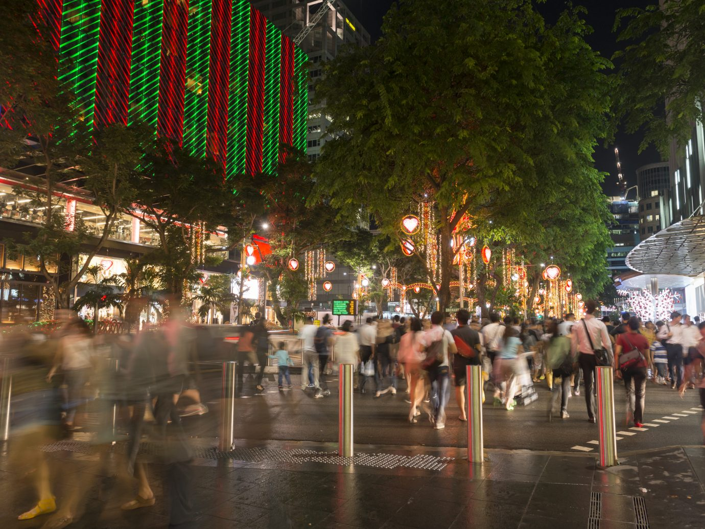 """Shoppers, tourists, walking on the pedestrian crossing in the night after a rain, enjoying the view of Christmas light up along Orchard Road. Singapore Shopping Centres, hotels and the street are light up for Christmas during this festive season."""