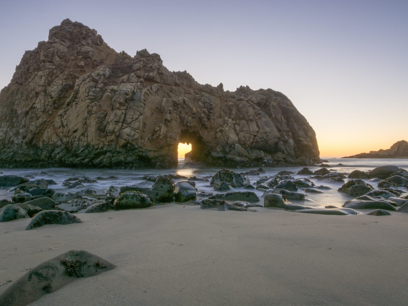 Setting sun glows through the keyhole at Pfeiffer Beach
