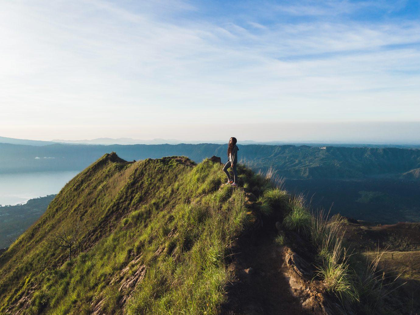 beautiful woman at the top of Mount Batur, Bali, Indonesia. Mountain hiking at sunrise
