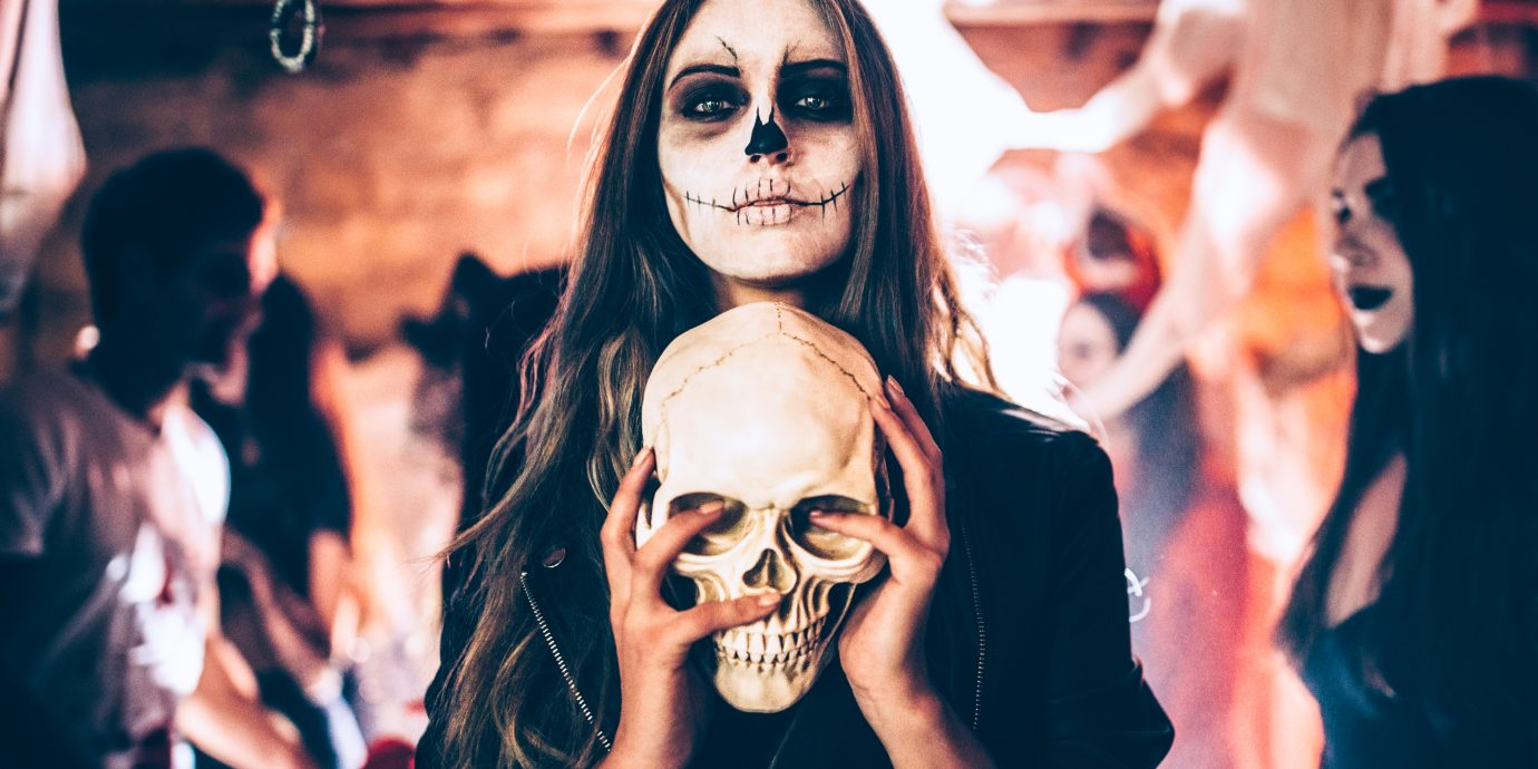 Halloween costume ideas, Young woman with santa-muerte make-up and disguise holding skull at Halloween dungeon party