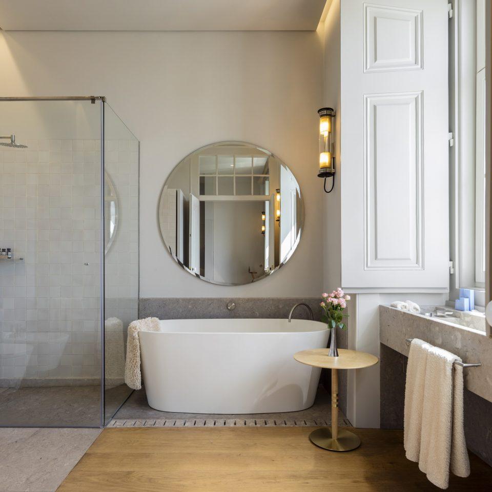 Bathroom interior with large circle mirror and bathtub at Verride Palácio Santa Catarina