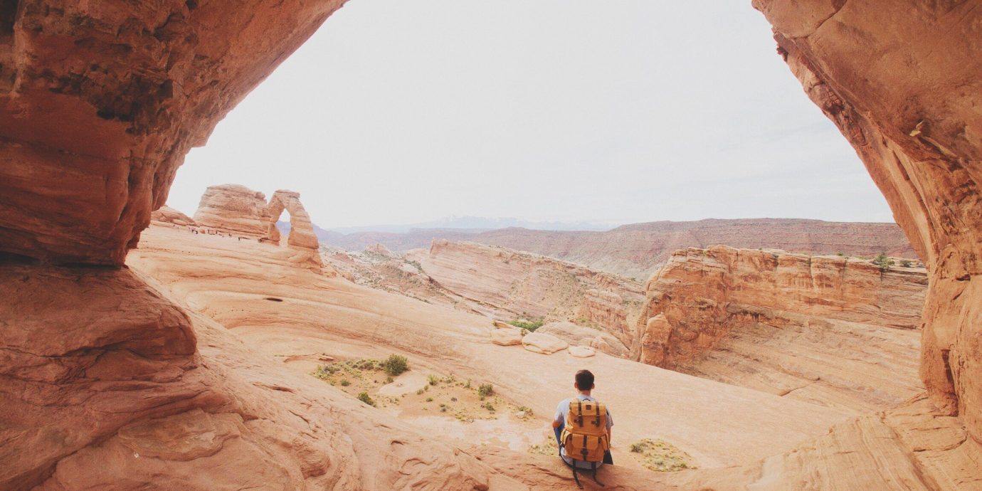Person in Arches National Park with backpack and travel gear