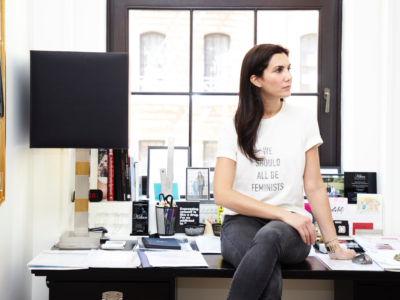 Elisabeth-Jones Hennessy sitting atop her desk in her work space