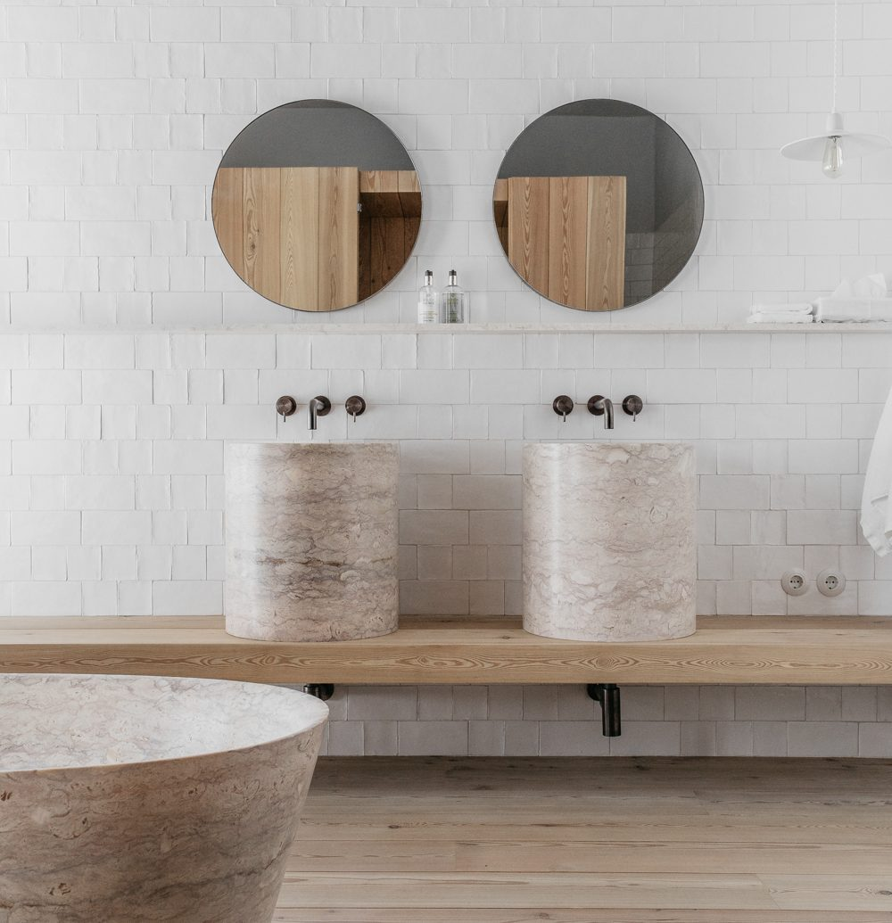 Two circular mirrors above two deep large marble sinks with a peak of the large marble bathtub
