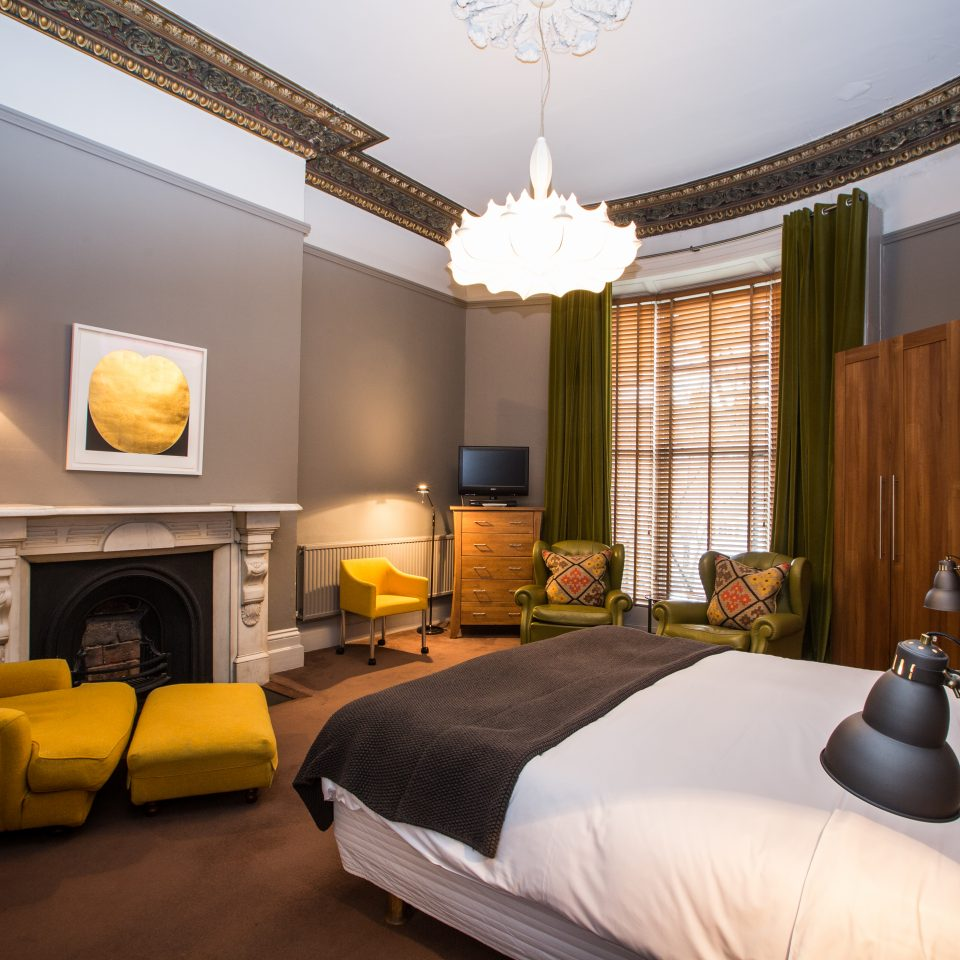 Room showing bed, small couch, and fireplace at Number 31 in Dublin