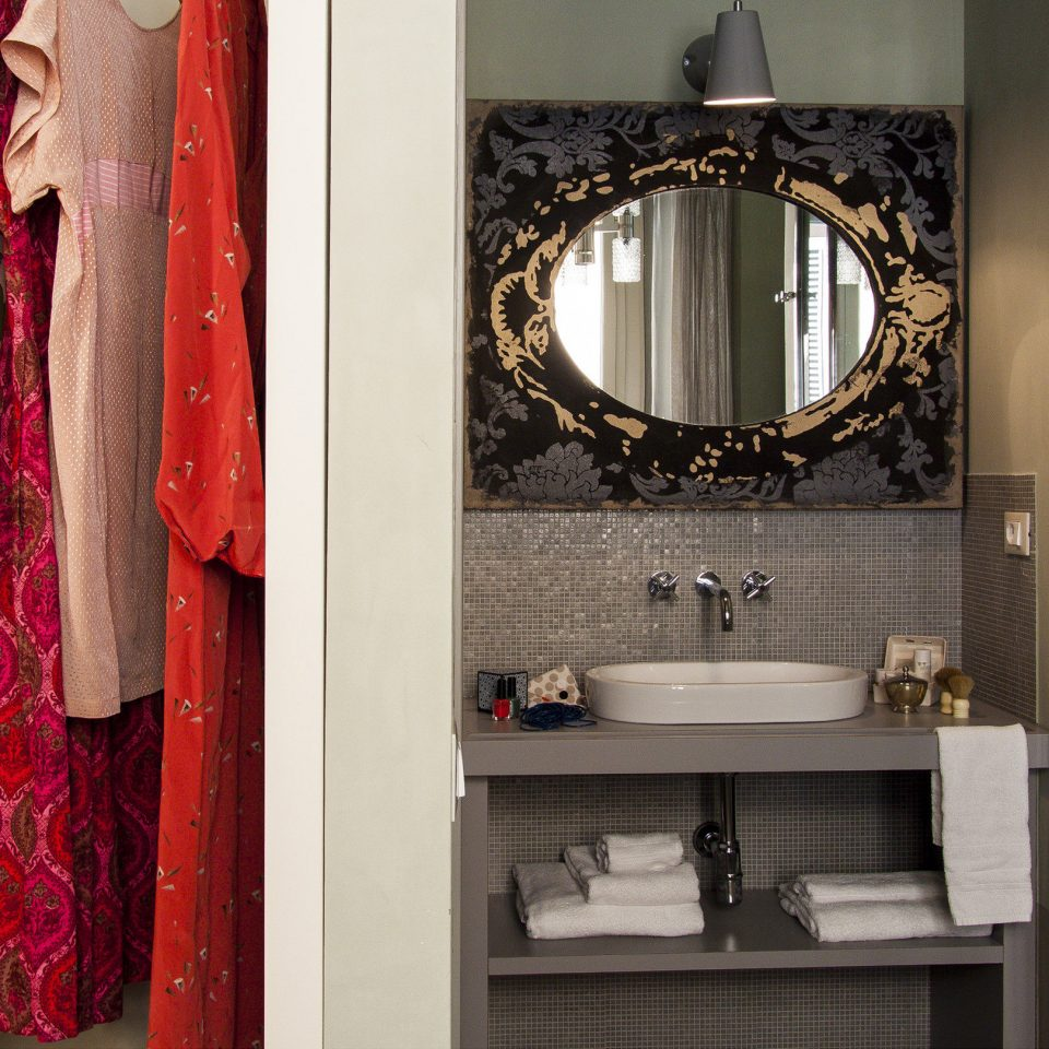 Sink, mirror, shower, and closet full of assorted hanging linens at Casacau