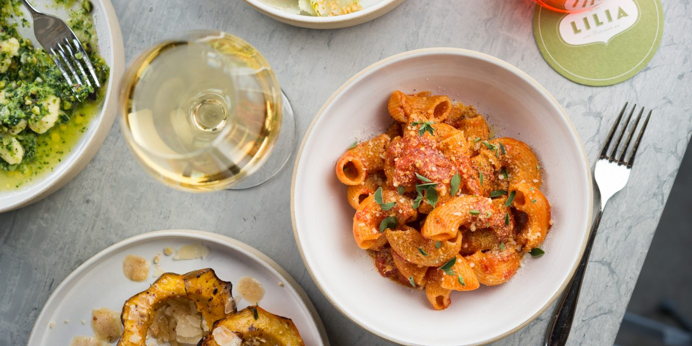 Assorted dishes including a pasta with red sauce and white wine