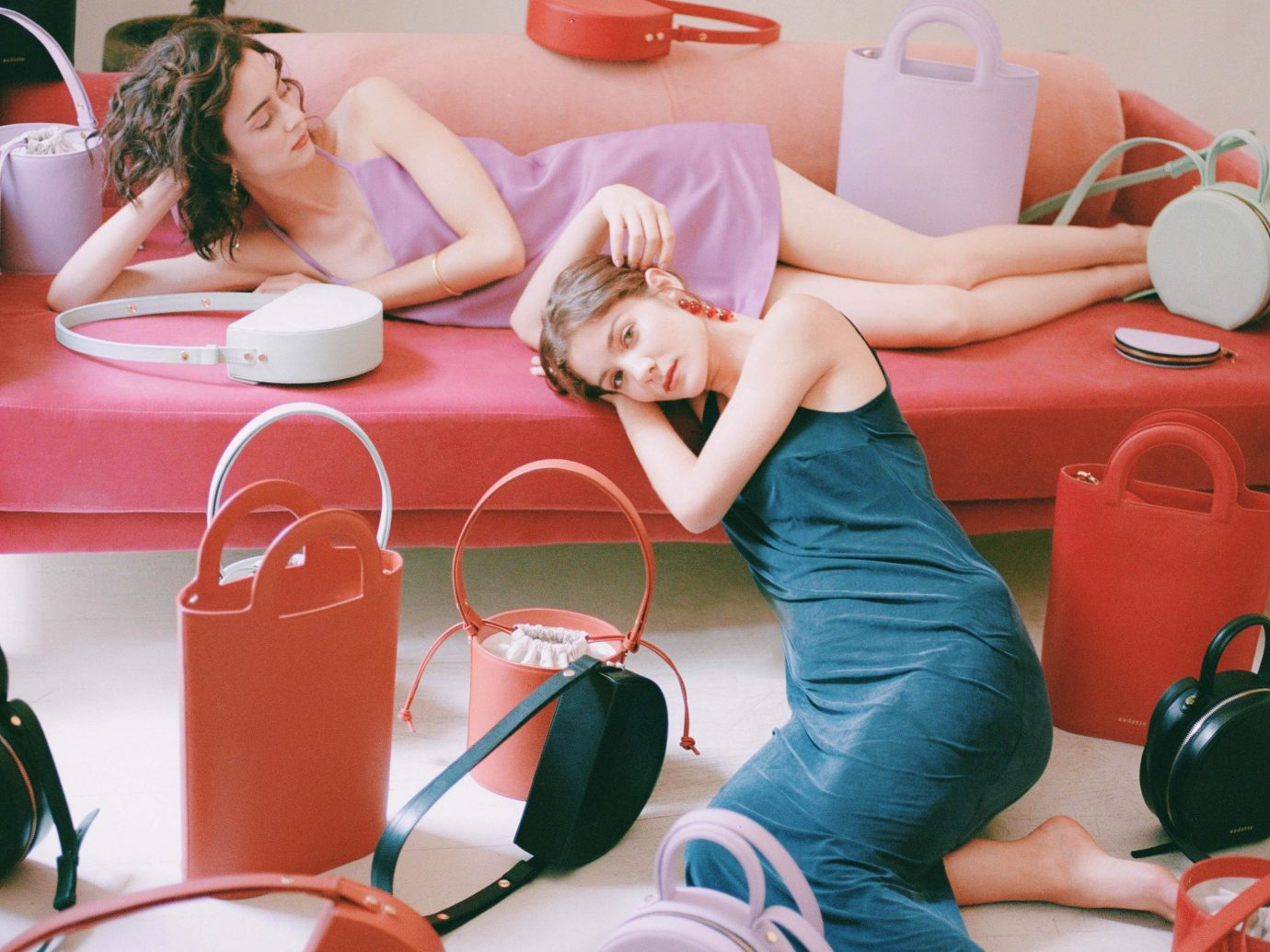 Two women modeling purses on a red couch