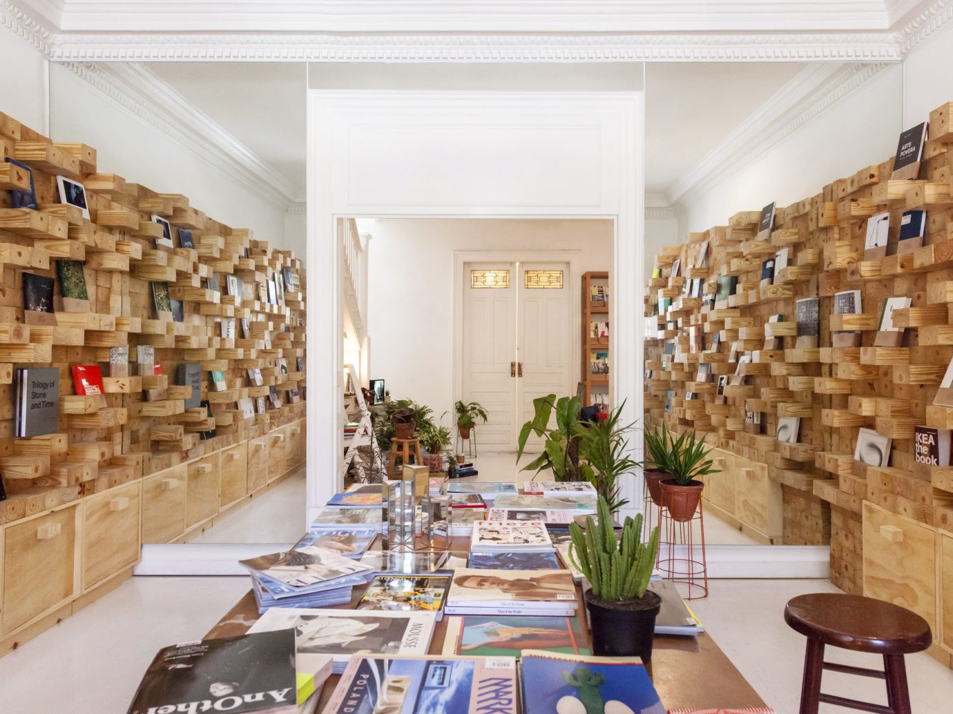 Interior of Casa Bosques in Mexico City with a table full of books and shelves on either sides of the walls